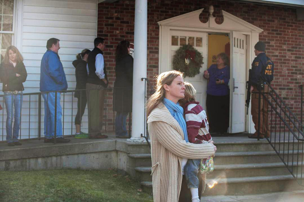 Description of . NEWTOWN, CT - DECEMBER 14:  A woman holds a child as people line up to enter the Newtown Methodist Church near the the scene of an elementary school shooting on December 14, 2012 in Newtown, Connecticut. According to reports, there are about 27 dead, 18 children, after a gunman opened fire in at the Sandy Hook Elementary School. The shooter was also killed.  (Photo by Douglas Healey/Getty Images)
