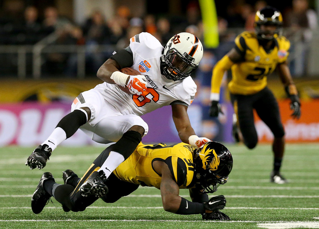 Description of . ARLINGTON, TX - JANUARY 03:  Ashton Lampkin #6 of the Oklahoma State Cowboys is tackled by E.J. Gaines #31 of the Missouri Tigers in the second quarter during the AT&T Cotton Bowl on January 3, 2014 in Arlington, Texas.  (Photo by Ronald Martinez/Getty Images)