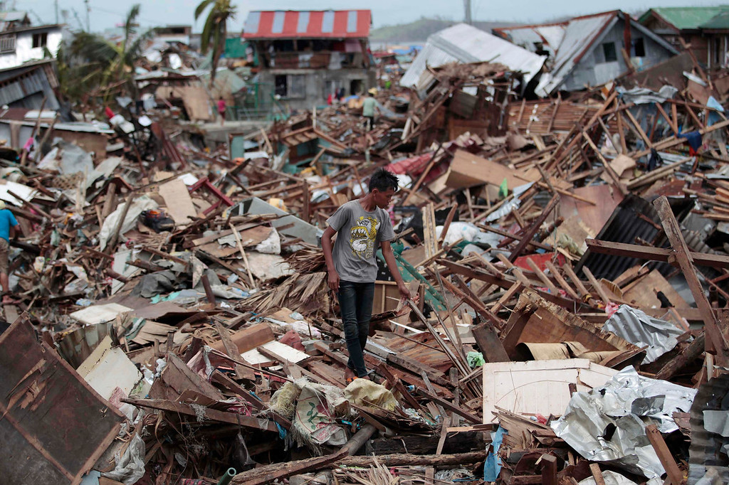 Description of . A Filipino man walks along debris from damaged homes at typhoon-hit Tacloban city, Leyte province, central Philippines on Wednesday, Nov. 13, 2013. Typhoon Haiyan, one of the strongest storms on record, slammed into six central Philippine islands on Friday leaving a wide swath of destruction. (AP Photo/Aaron Favila)
