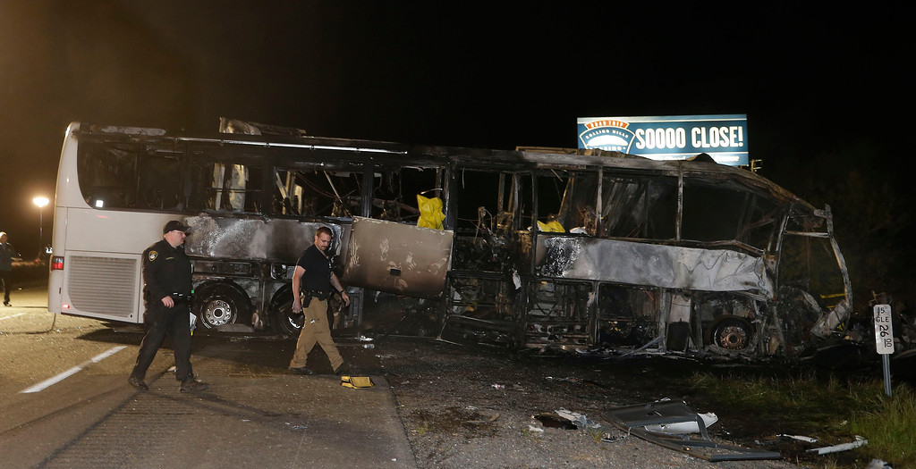Description of . A pair of California Highway Patrol Officers walk past the burned out tour bus where at least nine people died in a fiery crash between a tour bus and a FedEx truck on Interstate 5 Thursday, April 10, 2014, in Orland, Calif. (AP Photo/Rich Pedroncelli)