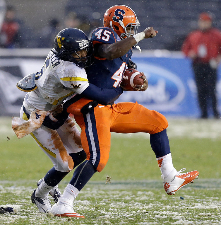 Description of . West Virginia cornerback Pat Miller, left, stops Syracuse running back Jerome Smith (45) during the first half of the Pinstripe Bowl NCAA college football game at Yankee Stadium in New York, Saturday, Dec. 29, 2012. (AP Photo/Kathy Willens)