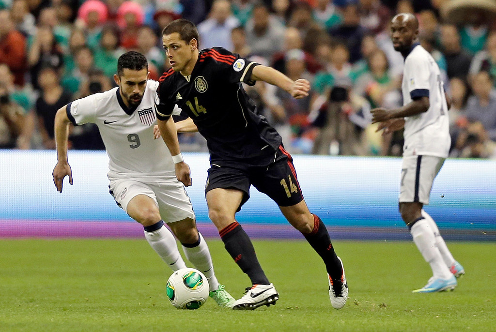 Description of . Mexico's Javier Hernandez, center, and United States' Herculez Gomez, left, vie for the ball during a 2014 World Cup qualifying match at the Aztec stadium in Mexico City, Tuesday, March 26, 2013. (AP Photo/Eduardo Verdugo)