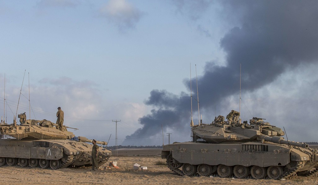 Description of . Israeli Merkava tanks are seen at an army deployment area near the border with the Gaza Strip, on July 31, 2014, as smoke billows from the coastal Palestinian enclave. Israel mobilised 16,000 additional reservists today to bolster forces fighting in Gaza as Washington gave its ally the go-ahead to raid stocks of emergency US weapons stored on Israeli soil.  AFP PHOTO/JACK GUEZ/AFP/Getty Images