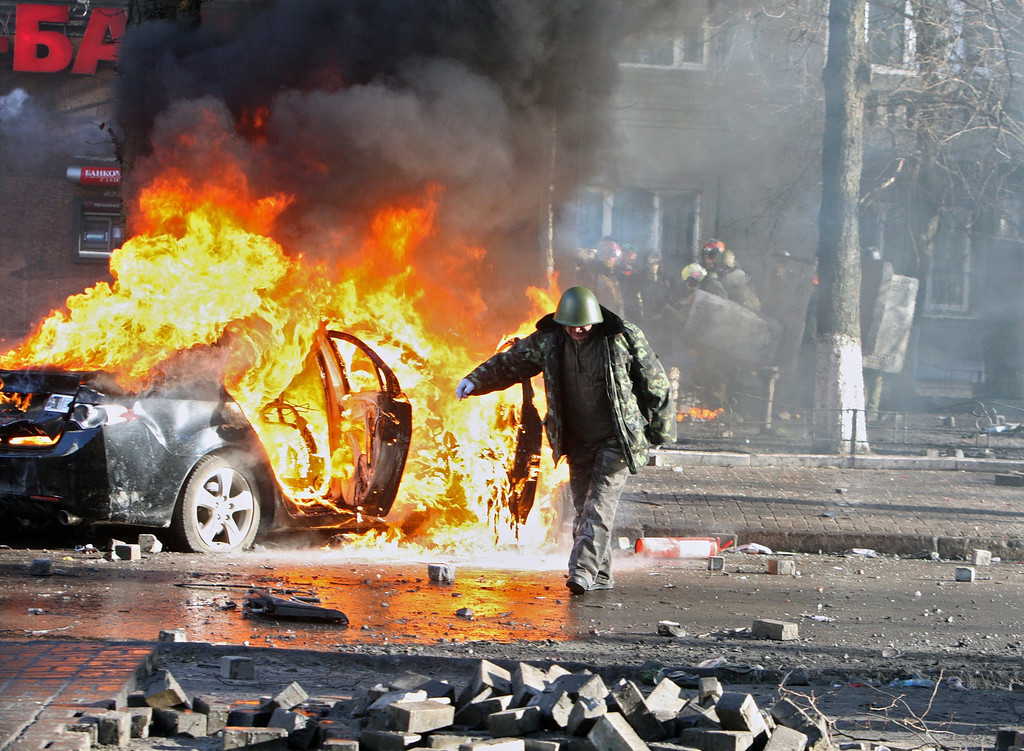 Description of . An protester walks by a burning car during an anti-government protest in downtown Kiev, Ukraine, 18 February 2014.  EPA/IGOR KOVALENKO
