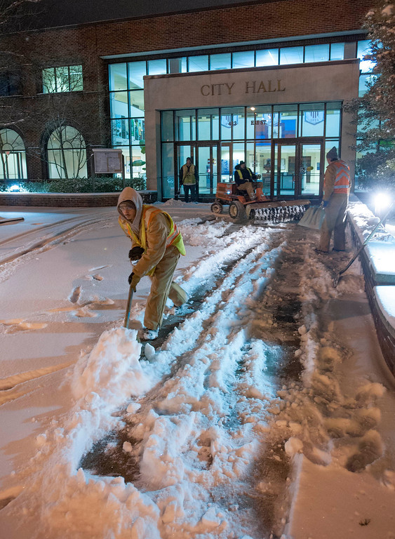 Description of . Fayetteville Parks and Recreation workers shovel the city hall sidewalk during the early morning hours of Wednesday Jan. 29, 2014. (AP Photo/The Fayetteville Observer, Johnny Horne)