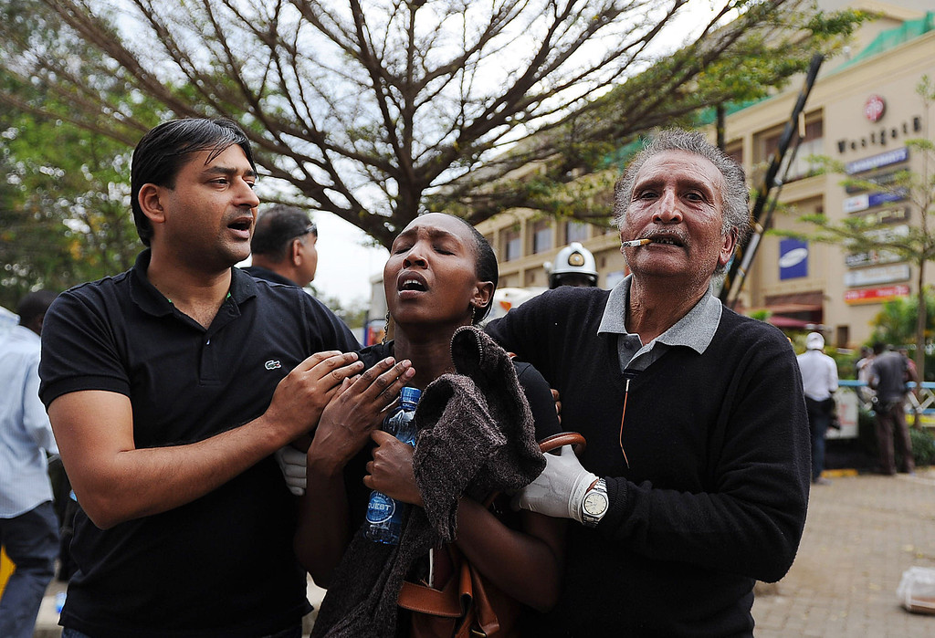 Description of . A woman (C) who had been held hostage reacts in shock on September 21, 2013 after she was freed following a security operation at an upmarket shopping mall in Nairobi where suspected terrorists engaged Kenyan security forces in a drawn out gun fight. Some 20 people have been killed and about 50 wounded Saturday in the initial attack by the gunmen the Kenya Red Cross said.  AFP PHOTO / Tony KARUMBA/AFP/Getty Images