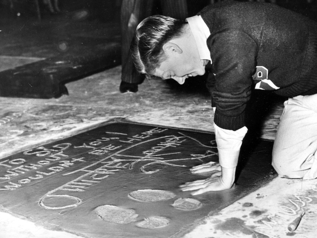 Description of . Mickey Rooney, 18-year-old film actor, singer and dancer, plants his hands into the cement next to his footprint and signature in the forecourt of Grauman's Theater on Hollywood Boulevard during induction ceremonies in Hollywood, Ca., on Oct. 19, 1938.  (AP Photo)