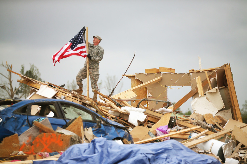Description of . Arkansas National Guard Staff Sgt. Skipper Smith hangs an American flag on a pole at the site of a home that was destroyed when a tornado hit the area April 29, 2014 in Vilonia, Arkansas.  (Photo by Mark Wilson/Getty Images)