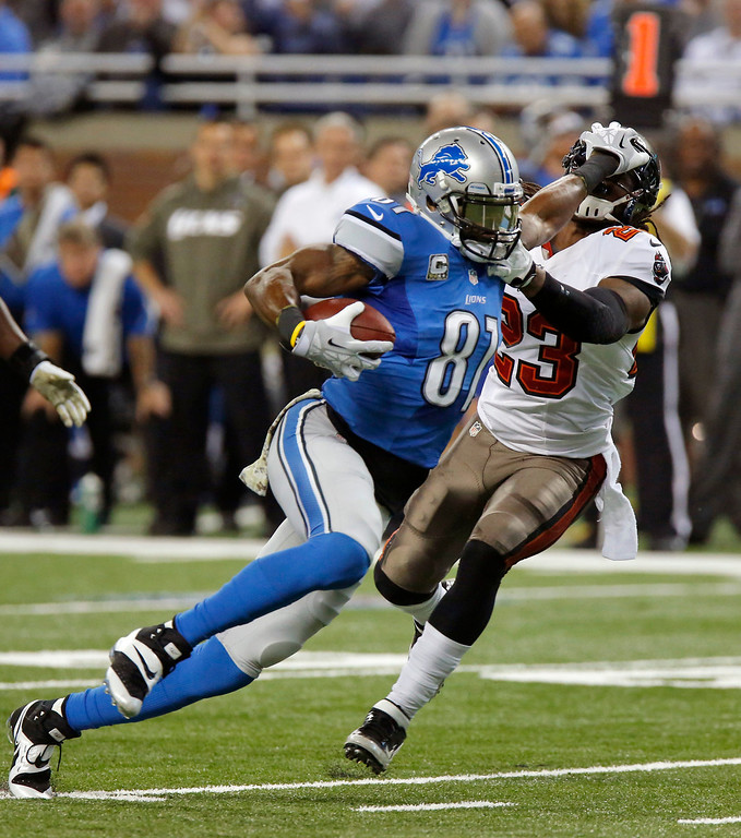 Description of . Detroit Lions wide receiver Calvin Johnson (81) stiff arms Tampa Bay Buccaneers strong safety Mark Barron (23) after a 19-yard reception during the second quarter of an NFL football game in Detroit, Sunday, Nov. 24, 2013. (AP Photo/Duane Burleson)