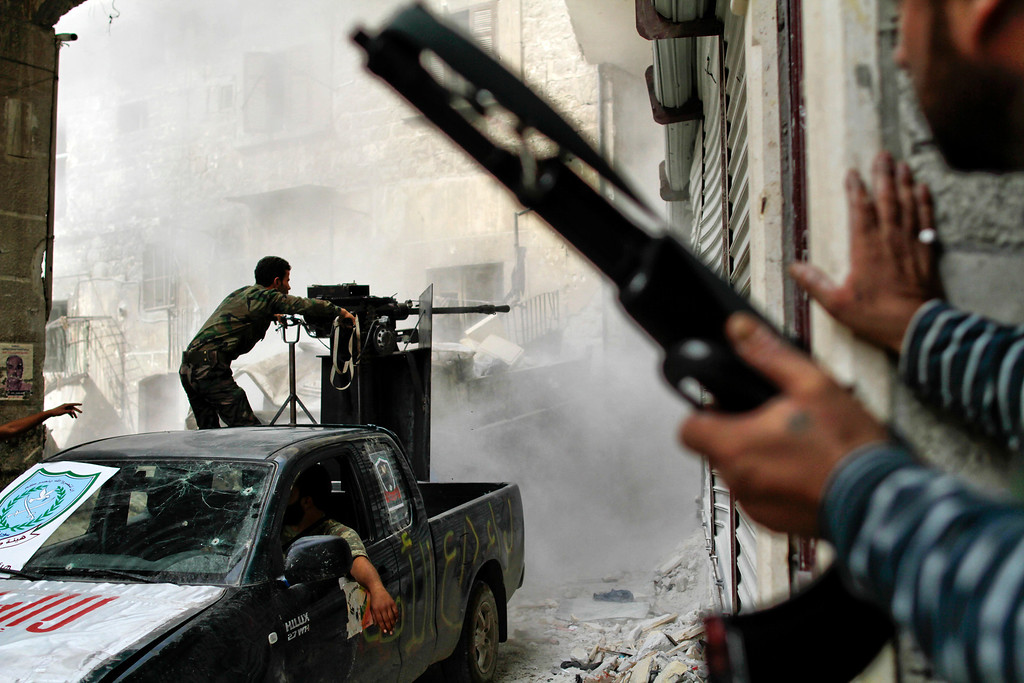 Description of . Free Syria Army (FSA) fighters battle with regime loyalist soldiers to dislodge a sniper from its position overlooking the two main roads in the neighbourhood of Askar in Syria's northern city of Aleppo on October 24, 2012. Javier Manzano/AFP/Getty Images