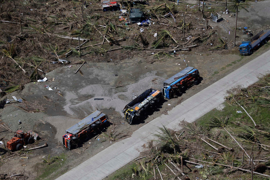 Description of . Cargo trucks lie on their side following last week's typhoon, in Leyte province, central Philippines, Friday, Nov. 15, 2013.  (AP Photo/Bullit Marquez)
