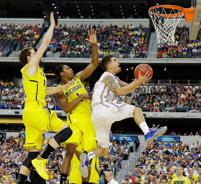 Description of . Florida\'s Scottie Wilbekin (5) shoots as Michigan\'s Glenn Robinson III (1) and Nik Stauskas (11) defend during the first half of a regional final game in the NCAA college basketball tournament, Sunday, March 31, 2013, in Arlington, Texas. (AP Photo/David J. Phillip)