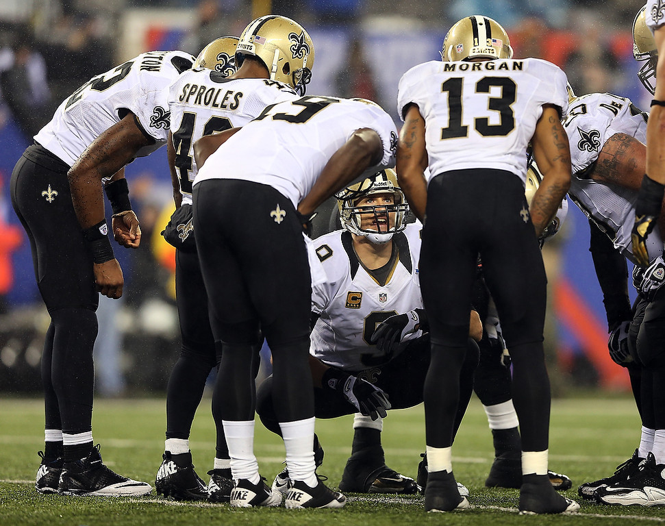 Description of . Drew Brees #9 of the New Orleans Saints talks in the huddle during the fourth quarter against the New York Giants on December 9, 2012 at MetLife Stadium in East Rutherford, New Jersey.  (Photo by Elsa/Getty Images)