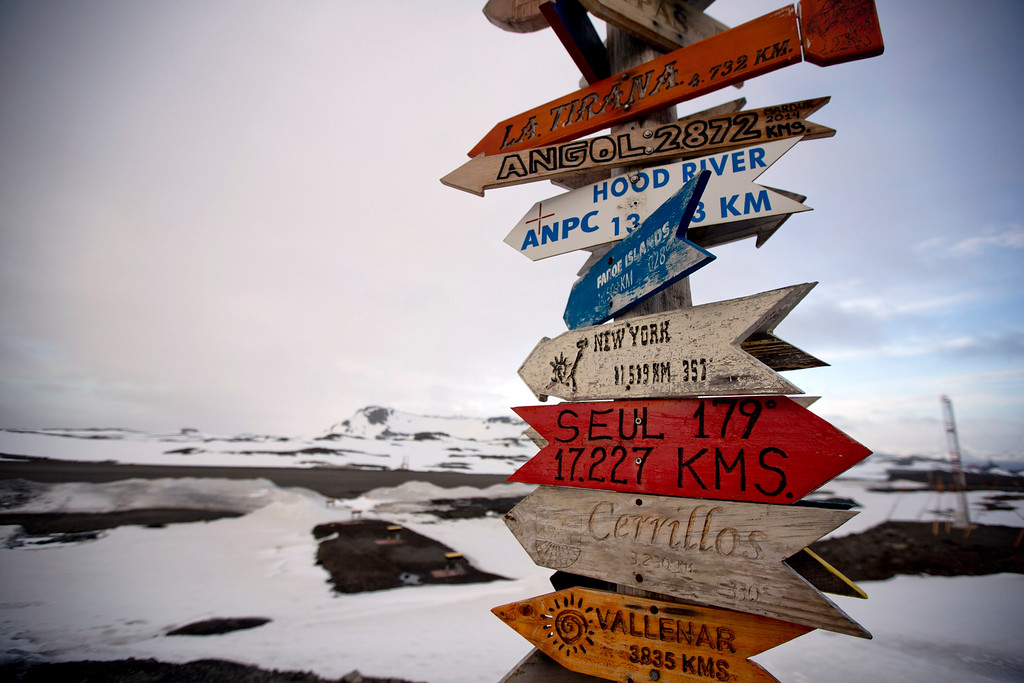 Description of . In this Jan. 20, 2015 photo, wooden arrows show the distances to various cities near Chile's Escudero station on King George Island, Antarctica. Thousands of scientists come to Antarctica for research. There are also non-scientists, chefs, divers, mechanics, janitors and the priest of the worldís southernmost Eastern Orthodox Church on top of a rocky hill at the Russian Bellinghausen station. (AP Photo/Natacha Pisarenko)