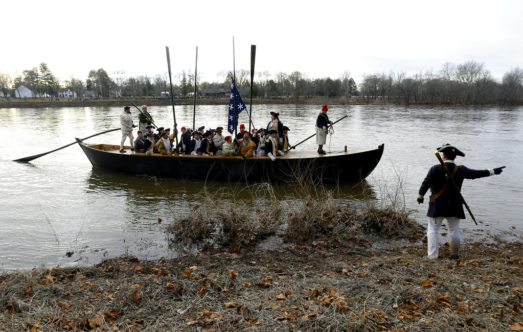 Description of . A boat containing George Washington, played by John Godzieba, approaches the riverbank on the New Jersey side after a crew of re-enactors crossed the Delaware River from Pennsylvania during the 61st annual re-enactment of Washington's daring Christmas 1776 crossing of the river, the trek that turned the tide of the Revolutionary War, in Washington Crossing, N.J. During the crossing 237 years ago, boats ferried 2,400 soldiers, 200 horses and 18 cannons across the river, and the troops marched eight miles downriver before battling Hessian mercenaries in the streets of Trenton. (AP Photo/Julio Cortez)