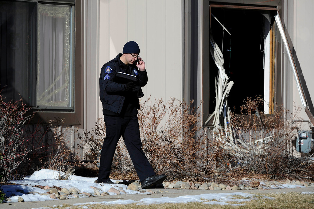 Description of . An Aurora Police officer comes out of a town home next to a crime scene at 16005 Ithaca Place in Aurora Saturday afternoon. The bodies of four people, including a gunman are dead at the scene following a standoff situation early Saturday morning. The Denver Post/ Andy Cross