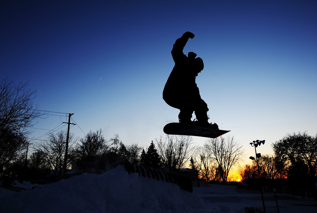 Description of . Despite cold temperatures, Tyler Kremer, 19, of Sioux Falls, catches some air while snowboarding at Terrace Park in Sioux Falls, S.D. as the sun sets in the background on Thursday evening, Dec. 5, 2013.  Winter storm and ice warnings are in effect through much of today for parts of six states in the Midwest. (AP Photo/Argus Leader, Joe Ahlquist)