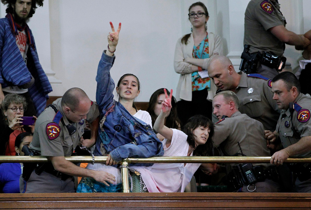 Description of . Abortion rights activists disrupt the special session of the Senate to consider legislation restricting abortion rights as they chain themselves to the railing in Austin, Texas July 12, 2013. The Republican proposal that would ban most abortions in Texas after 20 weeks of pregnancy moved toward a possible final vote in the state Senate Friday, and Democrats fiercely opposed to the measure conceded they will not be able to stop it.   REUTERS/Mike Stone