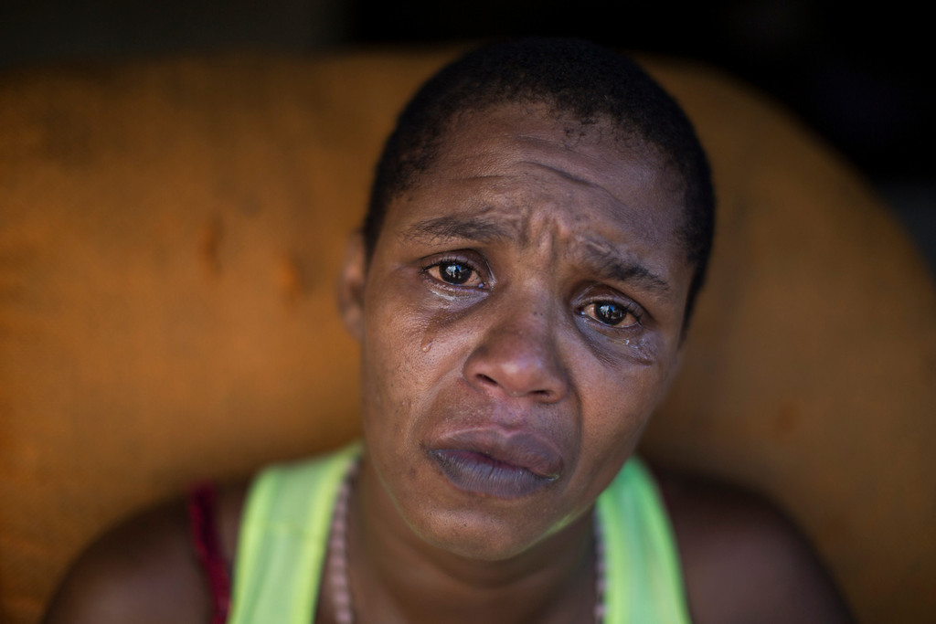. Luiza Lopes, 32, cries for her son at the Mare slum complex in Rio de Janeiro, Brazil, Saturday, April 5, 2014. According to Luiza she was not allowed to take her 9th son home after she gave birth to him because of her drug issues. According to her she went to treatment and is not using drugs anymore but her son remains in a shelter. More than 2,000 Brazilian soldiers stormed into the slum complex Saturday with armored personnel carriers and helicopters in a bid to improve security two months before the start of the World Cup. (AP Photo/Felipe Dana)