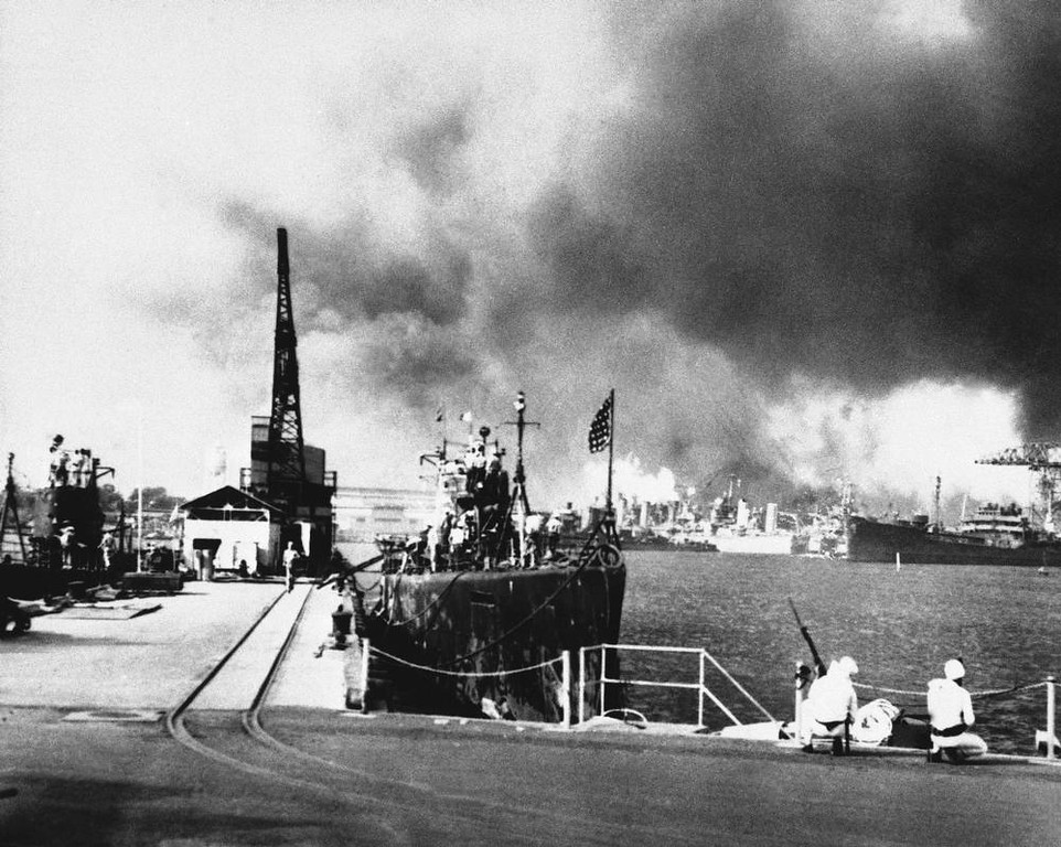 Description of . Smoke clouds the sky over Pearl Harbor as two sailors crouch with their rifles on a pier at the submarine base, trying desperately to locate an enemy to fire upon, Dec. 7, 1941. Submarines berthed nearby are USS Tautog and USS Narwhal. (AP Photo)
