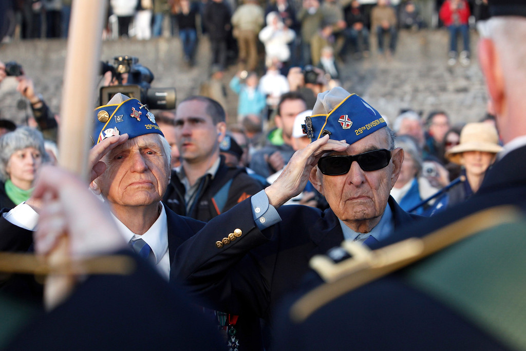 Description of . World War II veterans of the U.S. 29th Infantry Division, Hal Baumgarten, right, 90, of Pennsylvania, and Steve Melnikoff, 94, of Maryland, salute during a D-Day commemoration, on Omaha Beach in Vierville sur Mer, western France , Friday June 6, 2014. Veterans and Normandy residents are paying tribute to the thousands who gave their lives in the D-Day invasion of Nazi-occupied France 70 years ago. (AP Photo/Thibault Camus)