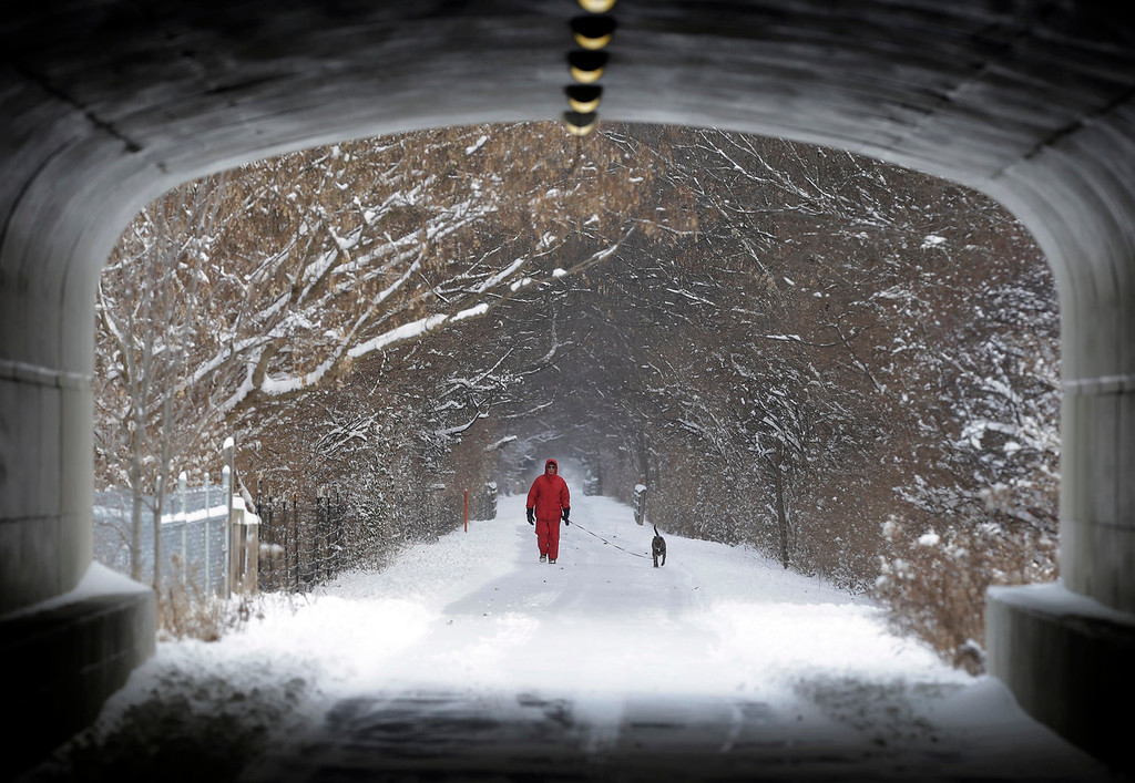 Description of . Naoom Haimson walks his dog, Molly, on the snow covered Monon Trail in Carmel, Ind., Thursday, Jan. 2, 2014. Over 5 inches of snow fell in Central Indiana. (AP Photo/Michael Conroy)