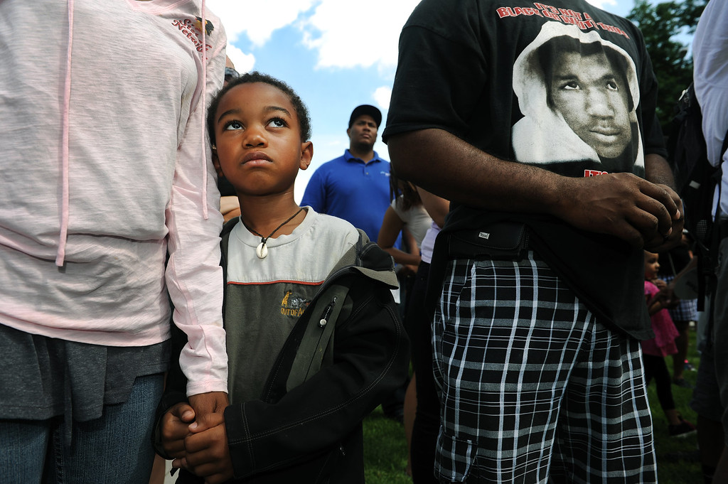 Description of . Simba Jones holds the hand of his mother Phoenix Jones, left hands during the rally in City Park in Denver, CO on July 14, 2013.  Several hundred people turned out  to show their disappointment in the acquittal of George Zimmerman in the murder trail of Trayvon Martin.  Zimmerman is the Florida man who shot and killed Trayvon Martin.
