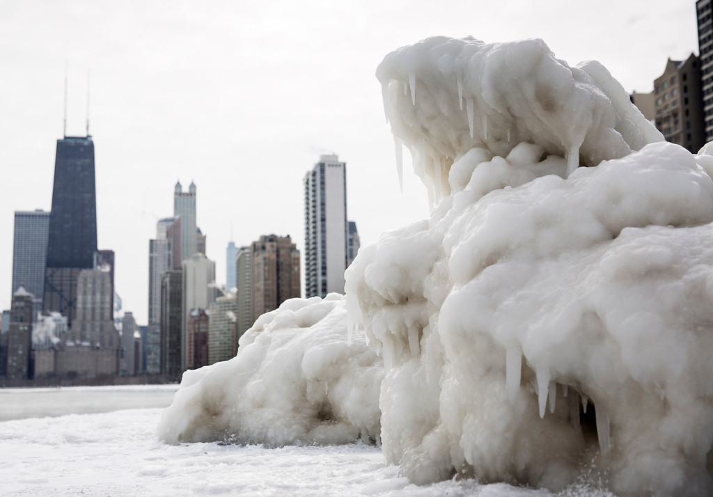 . The Chicago skyline is seen behind a large chunk of ice near North Avenue Beach as cold temperatures remain with wind chills nearing minus 30 Fahrenheit on Tuesday, Jan. 7, 2014, in Chicago. Dangerously cold polar air snapped decades-old records as it spread Tuesday from the Midwest to southern and eastern parts of the U.S. and eastern Canada, making it hazardous to venture outside and keeping many schools and businesses closed. (AP Photo/Andrew A. Nelles)