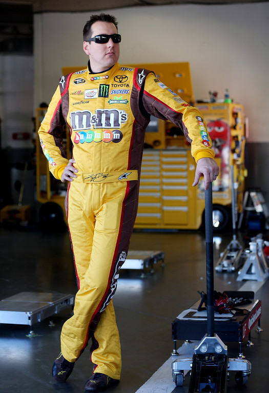 . DAYTONA BEACH, FL - FEBRUARY 20:  Kyle Busch, driver of the #18 M&M\'s Toyota, stands in the garage during practice for the NASCAR Sprint Cup Series Daytona 500 at Daytona International Speedway on February 20, 2013 in Daytona Beach, Florida.  (Photo by Matthew Stockman/Getty Images)