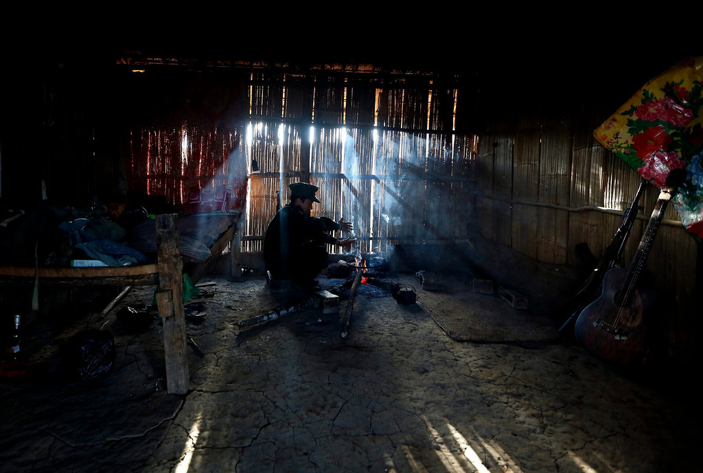 Description of . A soldier of the Kachin Independence Army (KIA) sits by the fire in Nanparkyaing village, Mantone Township, Northern Shan State, Myanmar. Myanmar's opium production in 2013 was expected to reach 870 tons, a 26-per-cent increase year-on-year, for a 13-per-cent increase in cultivated area, the United Nations said.  EPA/NYEIN CHAN NAING