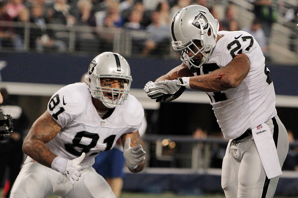 Description of . Oakland Raiders running back Rashad Jennings (27) celebrates his touchdown against the Dallas Cowboys with Mychal Rivera during the first half of an NFL football game, Thursday, Nov. 28, 2013, in Arlington, Texas.  (AP Photo/Brandon Wade)