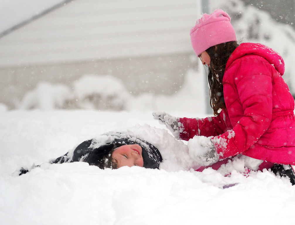 Description of . Ashton Lam, left, 8, is buried in the snow by friend Ava Miller, 10, as they enjoy the winter weather in Staunton, Va, on Wednesday, March 6, 2012. The March snowstorm is primarily hitting a region stretching from central Virginia to the northern and western portions of the state, where snow is piling up quickly. (AP Photo/The News Leader, Mike Tripp)