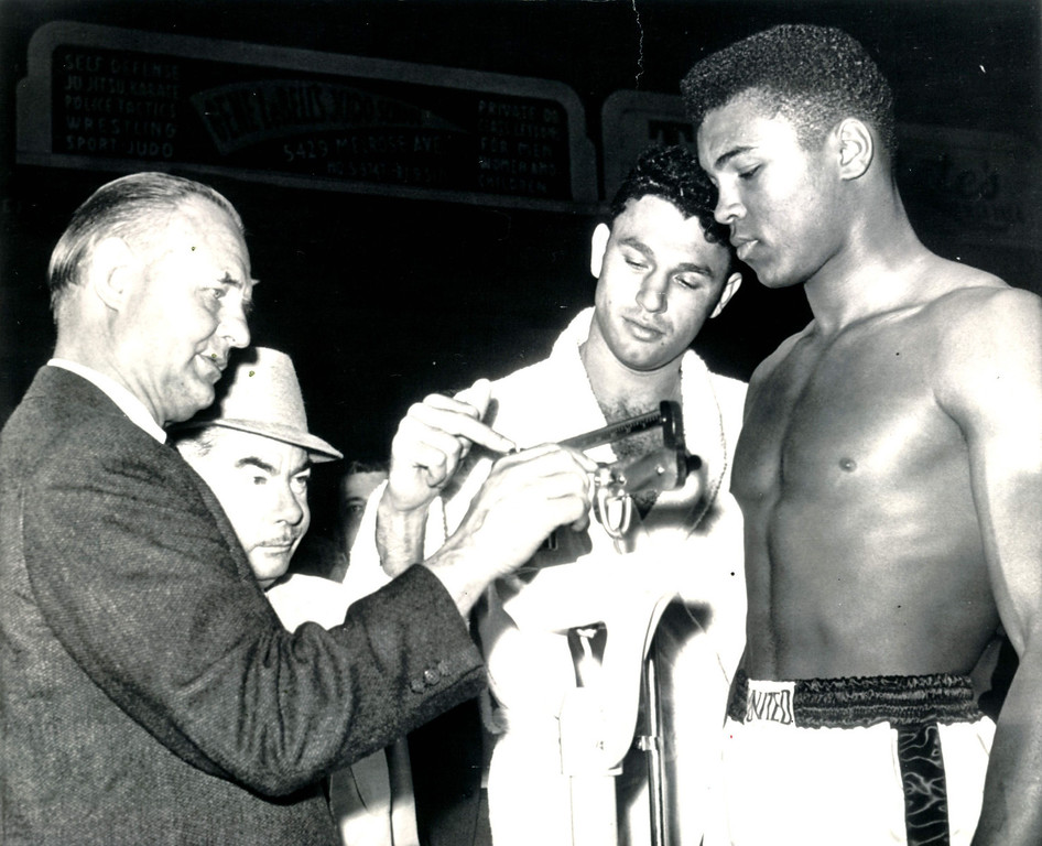 Description of . Alejandro Lavorante, Argentine heavyweight, lends a helping hand to Clayton Frye, secretary of the California Athletic Commission, as he weighs Cassius Clay of Louisville, Ky., for their 10-round fight in the Los Angeles Sports Arena tonight.  Clay weighed 199 pounds to Lavorante's 208. 1962. Credit: AP