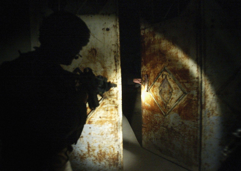 Description of . An american soldier of the 3rd Battalion of 21st Infantry Regiment prepares to enter a house as the door opens in the northern city of Mosul, March 03, 2005. As curfew goes into effect each night American solders come out looking for suspects and searching houses looking for weapons. In a conservative society like the one in Mosul, knocking on doors and searching houses in the middle of the night is believed to be a major source of anti-American feelings in the city. (Photo by Ghaith Abdul-Ahad/Getty Images).