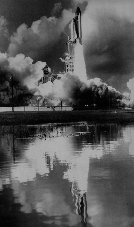 . The liftoff of the Space Shuttle Challenger on Oct. 30, 1985, a few months before it would explode with 7 crew members inside, is reflected in a ditch of water near the launch complex Wednesday at the Kennedy Space Center. The mission has a crew of eight and is scheduled to be in space for seven days.