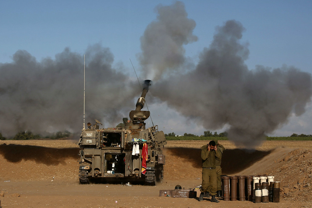 Description of . A 155mm artillery, positioned near the Israeli border with the Gaza Strip, fires a projectile towards targets in the Palestinian enclave, on July 17, 2014. Israel and the Islamist Hamas movement have agreed on a ceasefire that will begin at 0300 GMT on Friday, an Israeli official told AFP. AFP PHOTO /MENAHEM  KAHANA/AFP/Getty Images