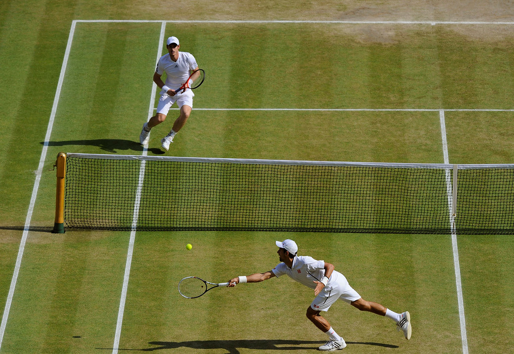 Description of . Novak Djokovic of Serbia, front, plays a return to Andy Murray of Britain during the Men's singles final match at the All England Lawn Tennis Championships in Wimbledon, London, Sunday, July 7, 2013. (AP Photo/Tom Hevezi, Pool)