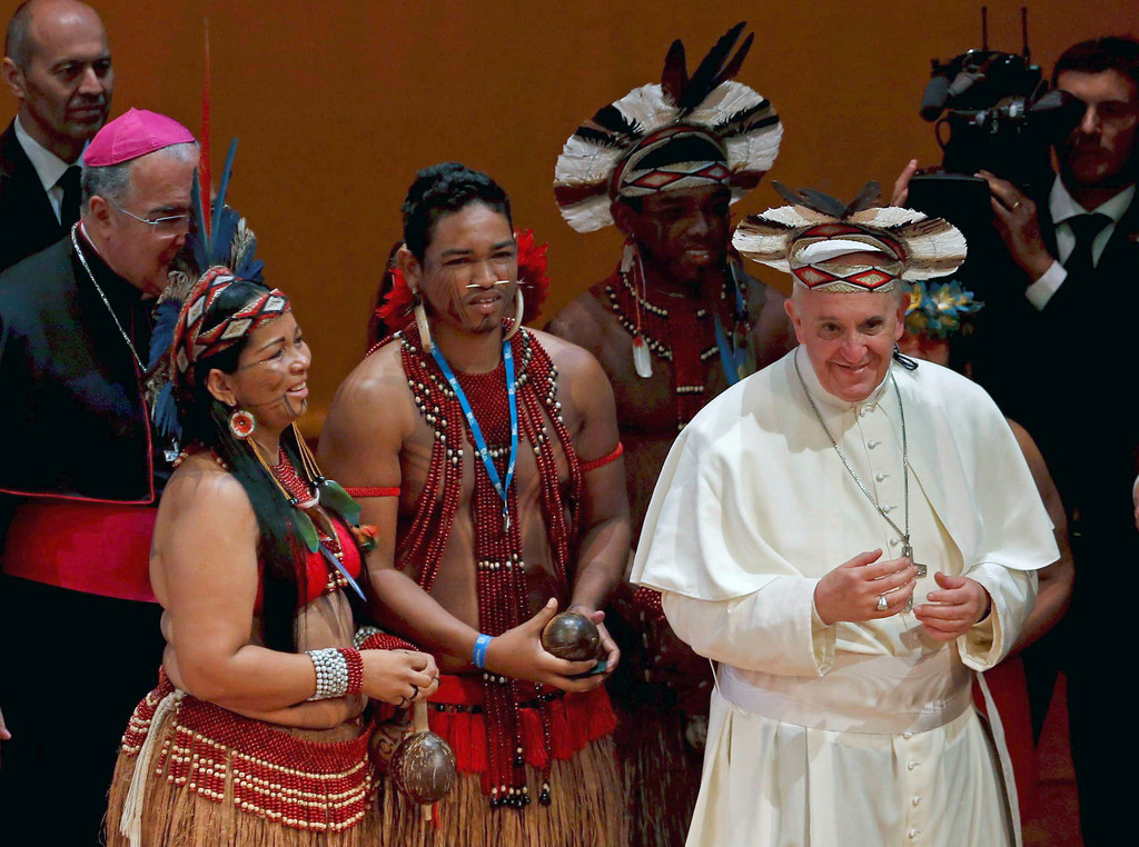 Description of . Pope Francis wears an indigenous headdress given to him by Ubirai Matos from the Pataxo tribe, fourth from left, after the pontiff spoke at Rio's Municipal Theater to an audience mostly made up of Brazil's political, business and cultural elite in Rio de Janeiro, Brazil, Saturday, July 27, 2013. Pope Francis is on the sixth day of his trip to Brazil where he will attend the 2013 World Youth Day in Rio. (AP Photo/Monica Imbuzeiro, Agencia O Globo)