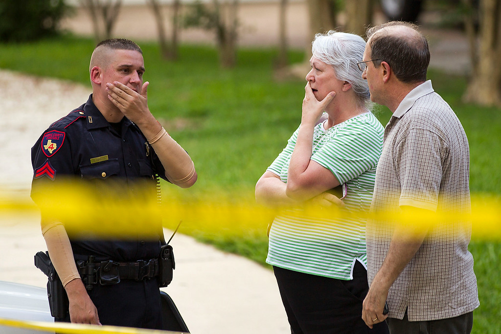 Description of . People stand with a law enforcement officer near the scene of a shooting Wednesday, July 9, 2014, in Spring, Texas. A Harris County Sheriff's Office statement says precinct deputy constables were called to the house about 6 p.m. Wednesday and found two adults and three children dead. Another child later died at a hospital. (AP Photo/Houston Chronicle, Brett Coomer)