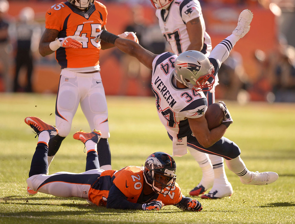 Description of . New England Patriots running back Shane Vereen (34) flies through the air after Denver Broncos free safety Mike Adams (20) hit him low during the second quarter. The Denver Broncos vs. The New England Patriots in an AFC Championship game  at Sports Authority Field at Mile High in Denver on January 19, 2014. (Photo by John Leyba/The Denver Post)