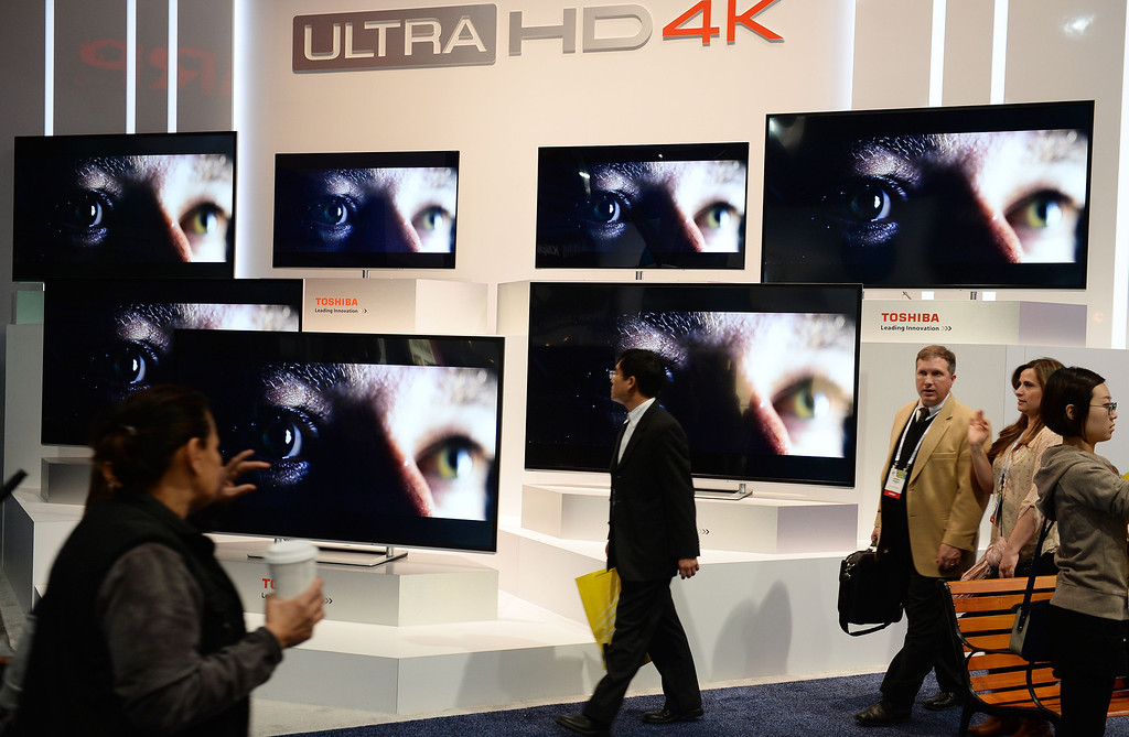 Description of . Attendees walk past the Toshiba Ultra HD 4K TV display at the 2014 International CES in Las Vegas, Nevada, January 8, 2014.  The Consumer Electronics Show, one of the largest in the world, runs from Jan 7-10. AFP PHOTO / Robyn Beck/AFP/Getty Images
