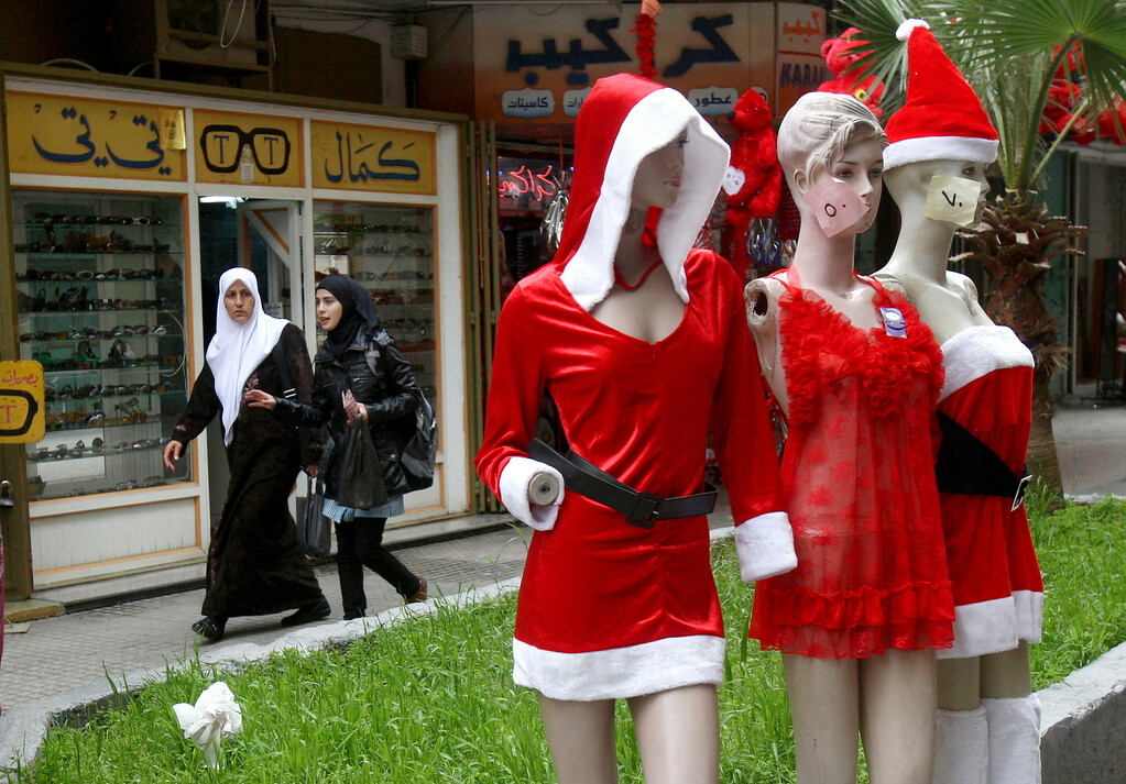 Description of . Palestinian women walk behind mannequins decorated for Valentine's Day, outside a shop in the West Bank city of Nablus, Thursday, Feb. 14, 2012. Valentine's Day is a festival of romantic love and is celebrated in many countries over the world by giving cards, flowers or gifts to spouses or partners. (AP Photo/Nasser Ishtayeh)