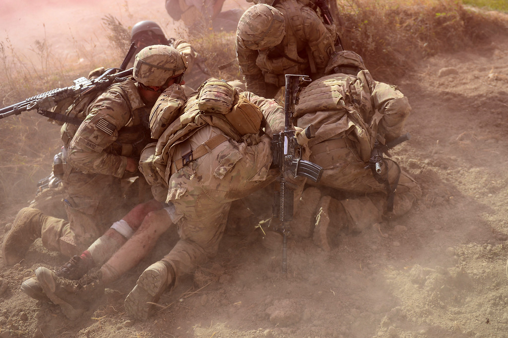 Description of . US Army soldiers attached to 2nd platoon, C troop, 1st Squadron (Airborne), 91st U.S Cavalry Regiment, 173rd Airborne Brigade Combat Team operating under NATO sponsored International Security Assistance Force (ISAF) protect a wounded comrade from dust and smoke flares after an Improvised Explosive Device (IED) blast during a patrol near Baraki Barak base in Logar Province on October 13, 2012. The soldier, 21 year-old Private Ryan Thomas from Oklahoma suffered soft tissue damage and after surgery in Afghanistan was scheduled to be evacuated to Germany. After 11 years of war, 2,135 US soldiers dead, their Afghan colleagues turning on them, and widespread predictions the conflict will end in failure, coalition forces could be forgiven for suffering a dip in morale. But commanders and soldiers on the ground insist the challenges are bringing them closer together, even if the outcome of the war is uncertain and the perception of what constitutes success has changed. (MUNIR UZ ZAMAN/AFP/Getty Images)
