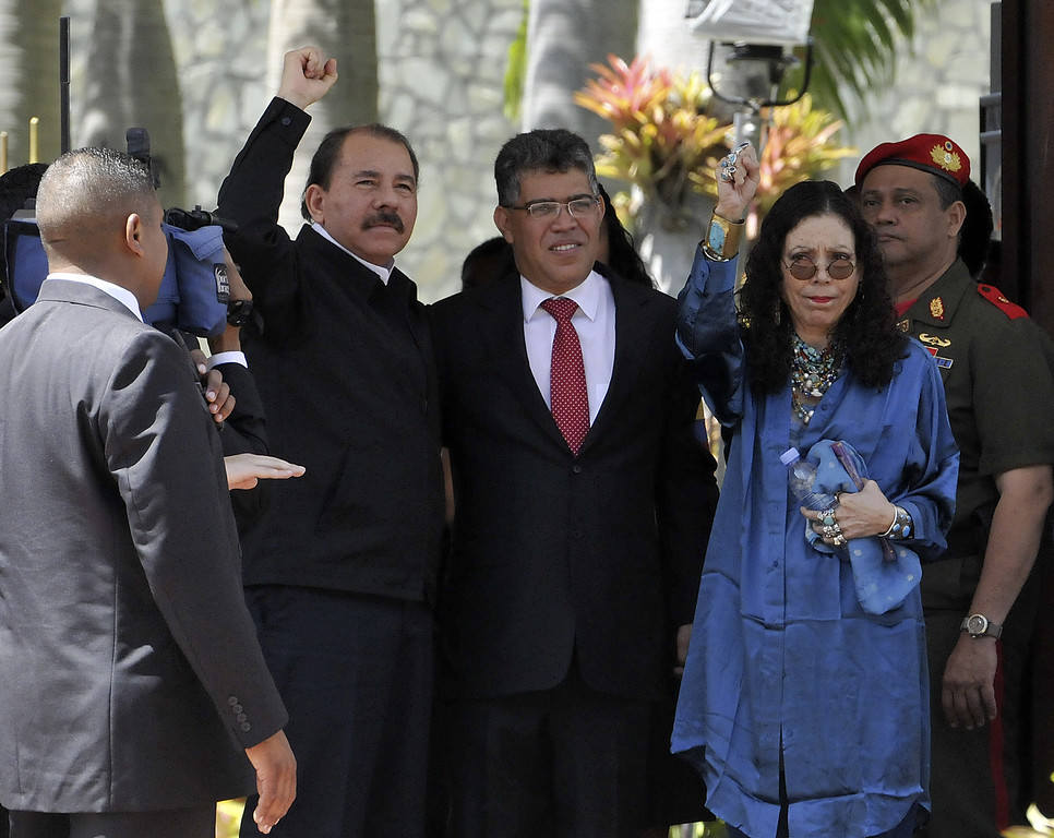 Description of . Nicaraguan President Daniel Ortega(L) raises his fist next to Venezuelan Foreign Minister Elias Jaua(C) and Nicaraguan first lady Rosario Murillo outside of the funeral of the late President Hugo Chavez, in Caracas, on March 8, 2013. AFP PHOTO/STRSTR/AFP/Getty Images