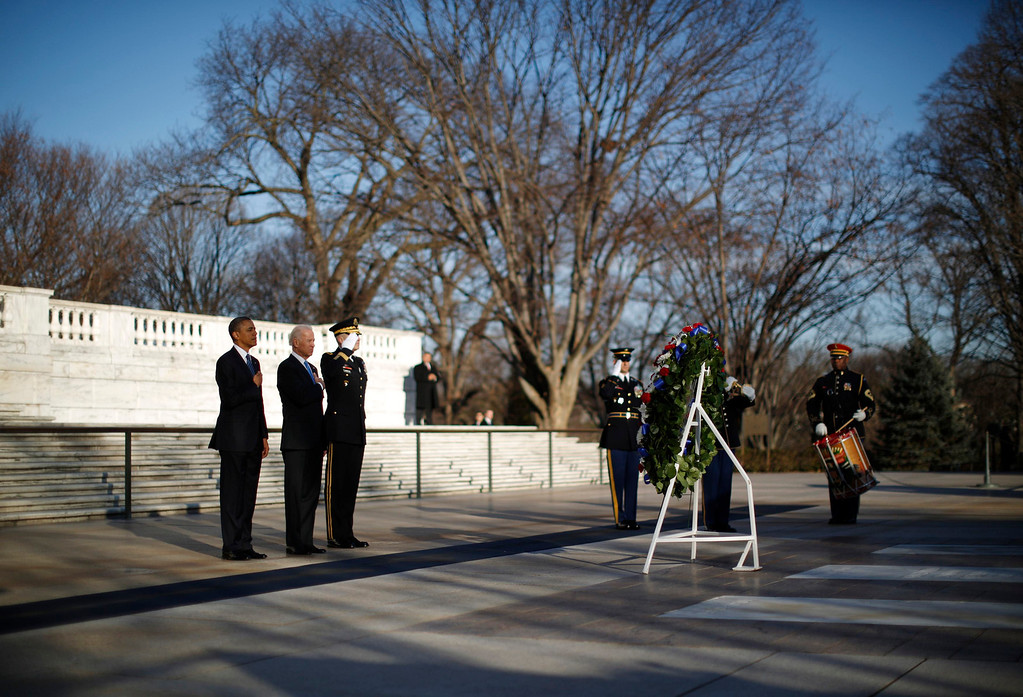 Description of . U.S. President Barack Obama and Vice President Joe Biden are pictured as they listen to taps being played after laying a wreath at the Tomb of the Unknown Soldier at Arlington National Cemetery near Washington, January 20, 2013. Obama will take the official oath of office in a small, private ceremony at the White House on Sunday, setting a more subdued tone for his second inauguration than his historic swearing-in four years ago. Following a wreath-laying ceremony at Arlington National Cemetery, Obama will be sworn in at the White House at 11:55 a.m. EST (1655 GMT).      REUTERS/Jason Reed