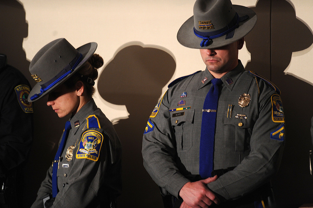 Description of . Members of the Connecticut state police bow their heads during a memorial service for victims of the Sandy Hook Elementary School shooting at Newtown High School in Newtown, Connecticut, U.S., on Sunday, Dec. 16, 2012. Obama arrived in Newtown, Connecticut, two days after the tragedy and as authorities were still trying to piece together a motive for the second-deadliest mass shooting in the U.S. Photographer: Olivier Douliery/Pool via Bloomberg