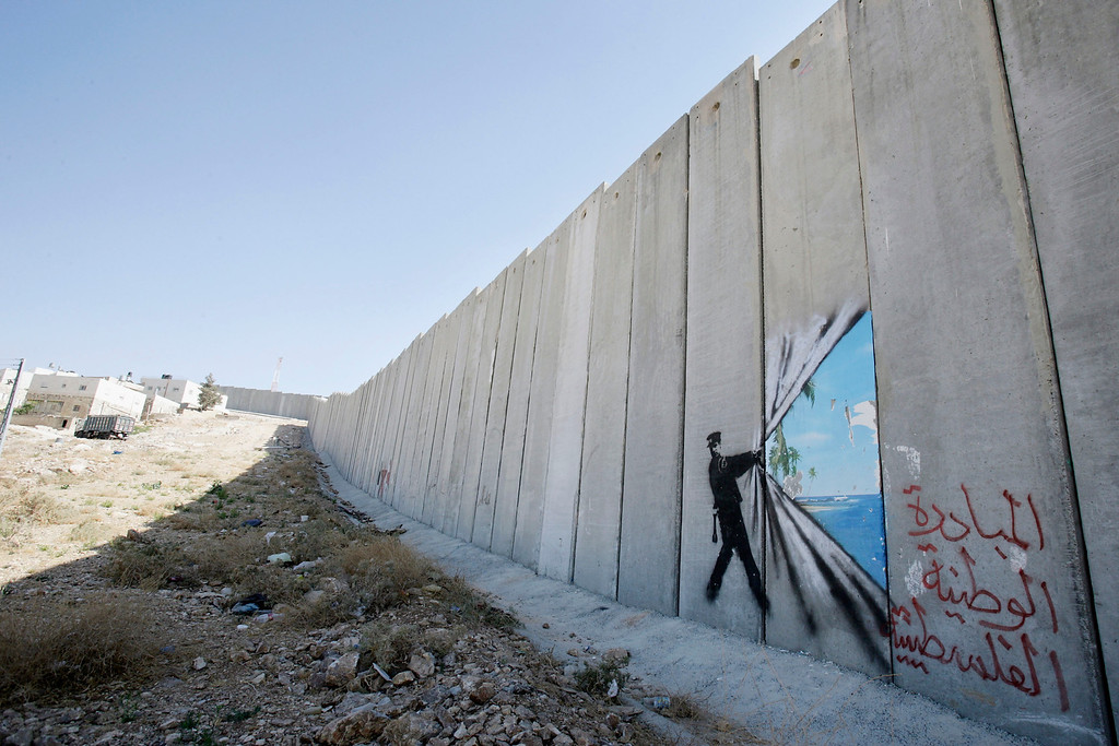 Description of . A graffiti made by the graffiti artist Banksy is seen on Israel's highly controversial West Bank barrier in Abu Dis on August 6, 2005. Banksy has made a name for himself with provocative images stencilled around the streets of London.On his recent trip to the Palestinian territories he has created nine of his images on Israel's highly controversial West Bank barrier. (Photo by Marco Di Lauro/Getty Images)