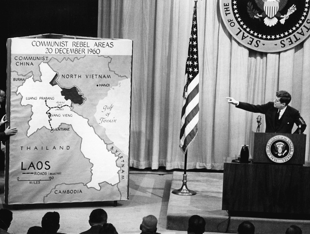 Description of . President Kennedy points to a map of Laos during a press conference in March 1961, saying that the communist threat to Laos wass