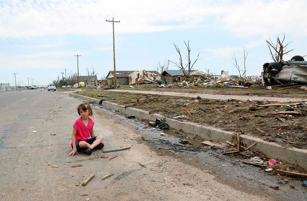 Description of . Abigail Stephan, 6, sits on the road waiting for her mother to show her their tornado-destroyed home on 6th Avenue for the first time since the storm in Moore, Oklahoma May 23, 2013. The tornado was the strongest in the United States in nearly two years and cut a path of destruction 17 miles long and 1.3 miles wide. REUTERS/Rick Wilking