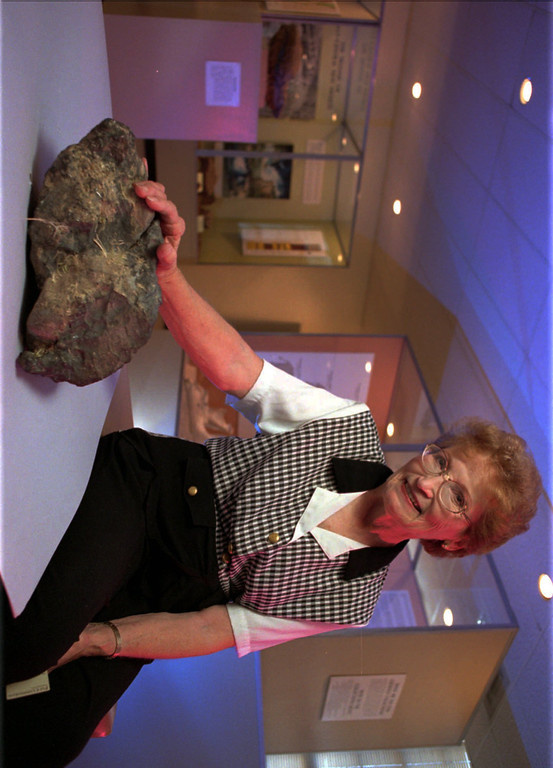 Description of . Nelda Wallace of Portales, N.M., poses next to a 37-pound meteorite at the University of New Mexico in Albuquerque, N.M., Tuesday June 23, 1998, The meteorite, believed to be about 4.5 billion years old, landed in the back of her home early Saturday June 13, 1998.  University of New Mexico scientists say it's probably the largest meteorite ever to fall in New Mexico.  (AP Photo/Pat Vasquez-Cunningham)